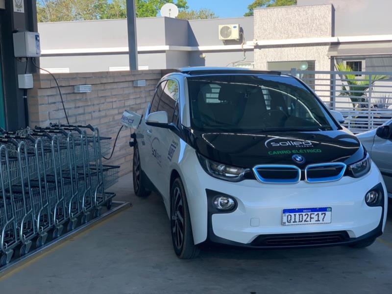 Carro elétrico abastecendo e usina solar instalada no supermercado