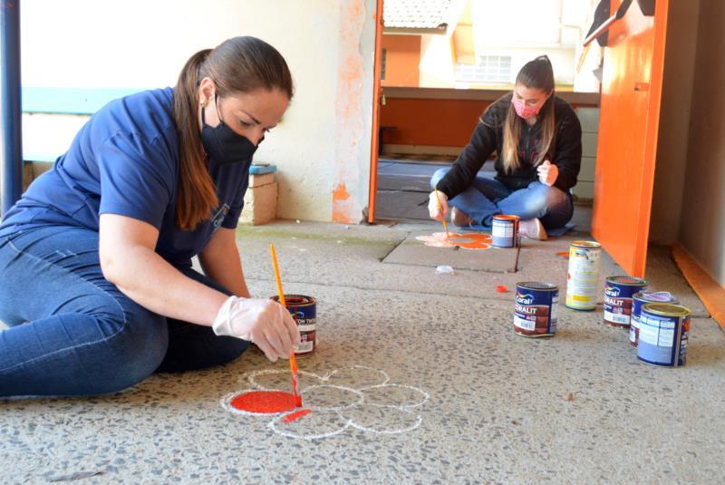 Escola pinta flores no chão para demarcar distanciamento