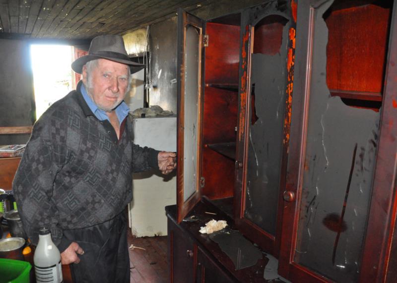 Gerhard ao lado do armário que foi destruído pelo fogo na manhã da última sexta-feira
