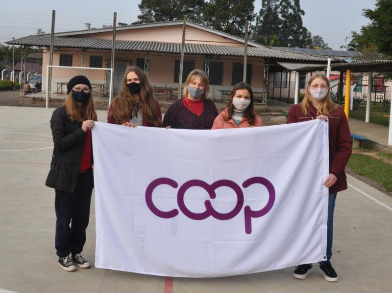 Estudantes e professora orientado exibem bandeira da cooperativa