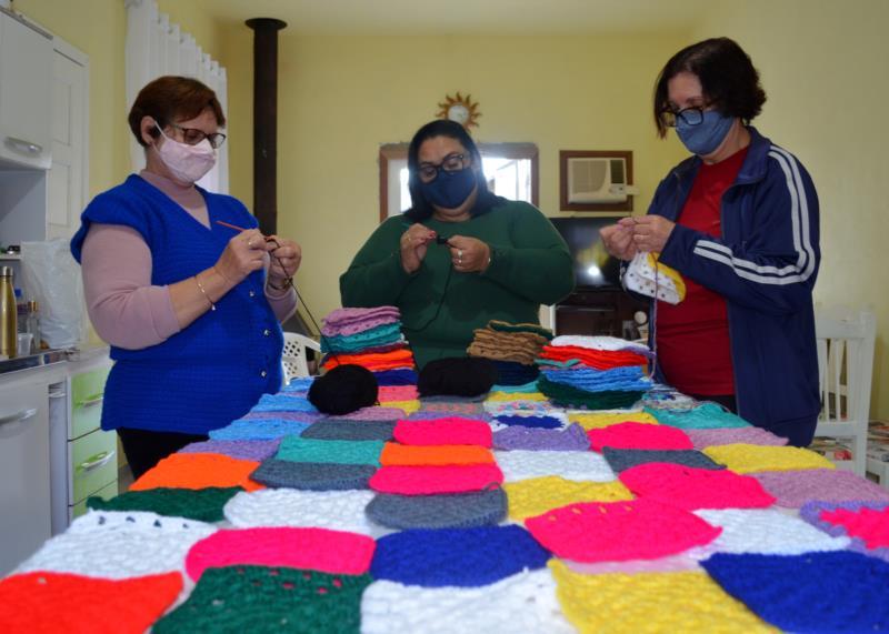 Participantes da oficina confeccionam quadrados de crochê que viram cobertores