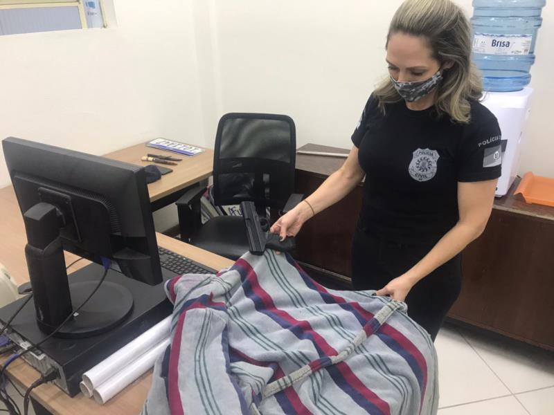 Delegada Ana Luísa com o roupão e a arma de airsoft apreendida