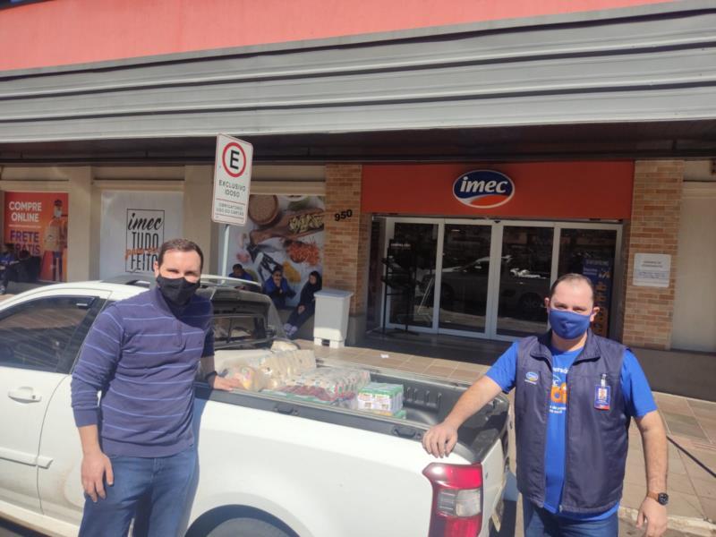 Gerente do Imec Supermercados de Santa Cruz do Sul entregando os mais de 400 quilos de alimento ao presidente do Rotaract, Grasiel Grasel