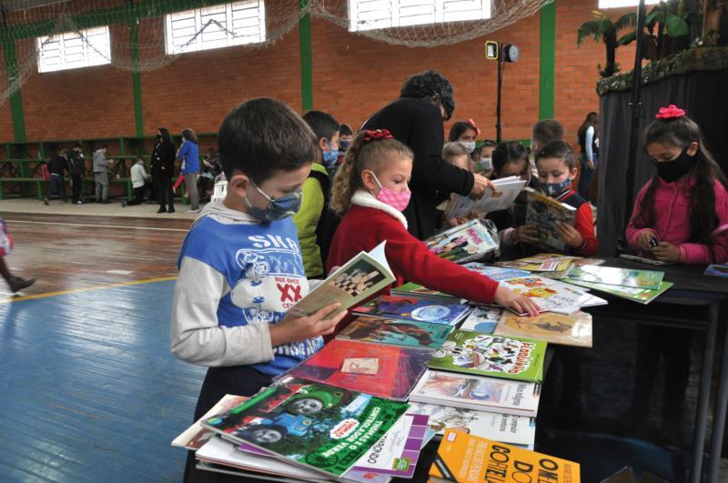 Na banca de livro, Mateus procurava um livro interessante para ler na escola e em casa